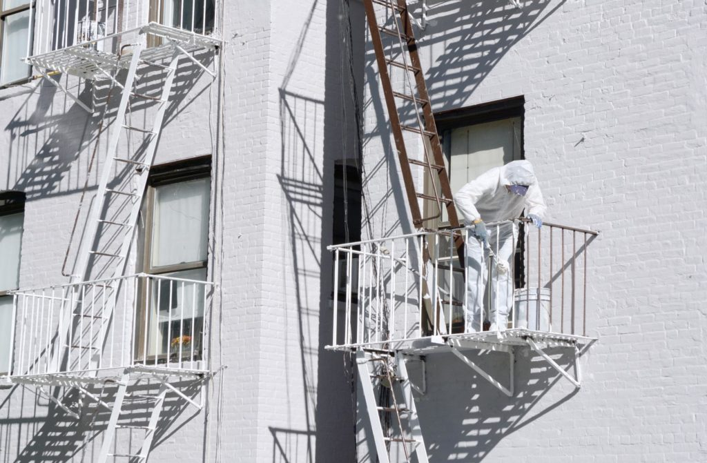 man with full suit painting the emergency metal stair case