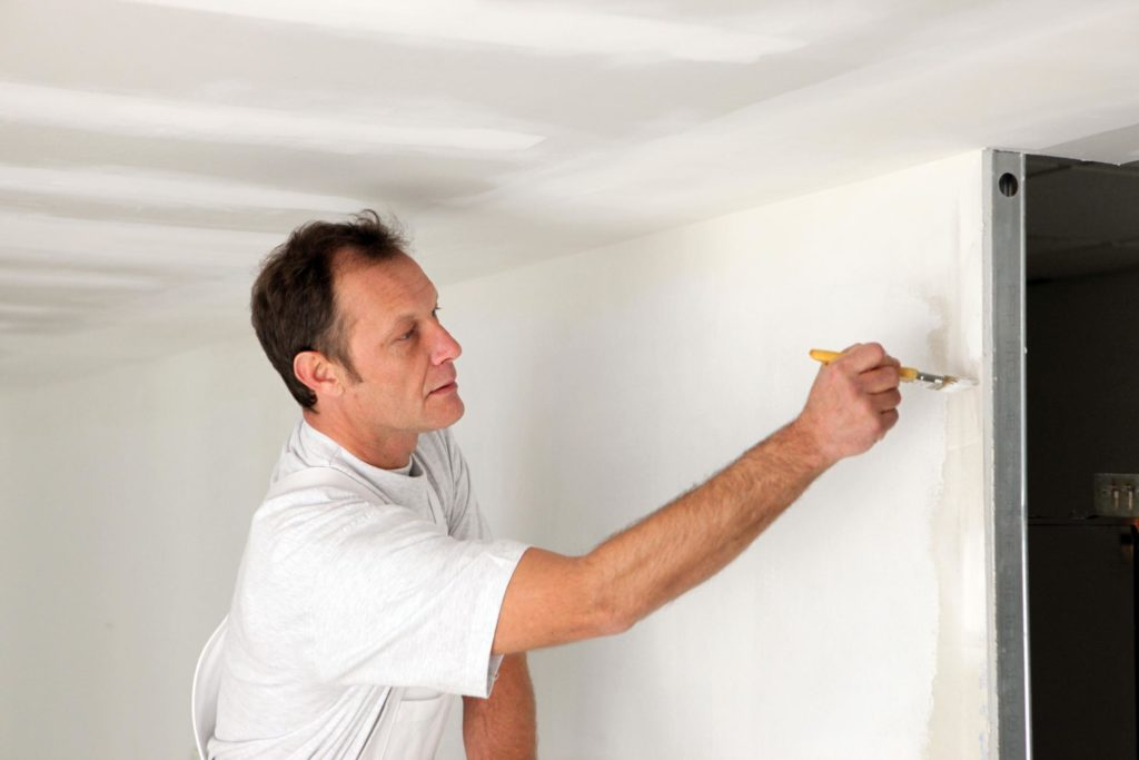 man painting the wall using paint brush
