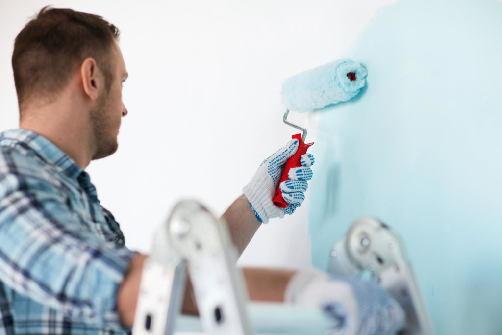 man painting the wall color sky blue