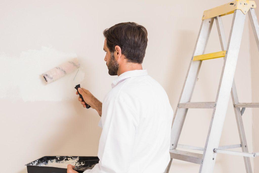 man painting the interior wall